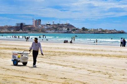 A happy man sells ice cream on the beach.