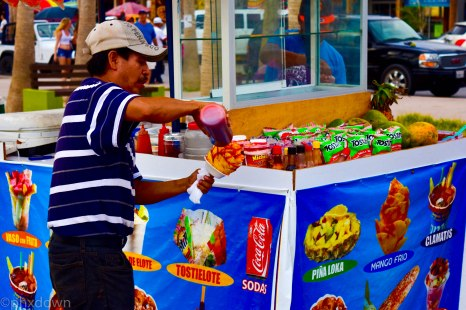 A vendor makes a mango pinecone with chili powder and fruit sauce drizzle. Mexico is so colorful.